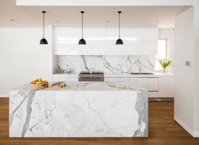 marble kitchen island and backsplash, wooden floor, pictures of kitchen islands, white cabinets