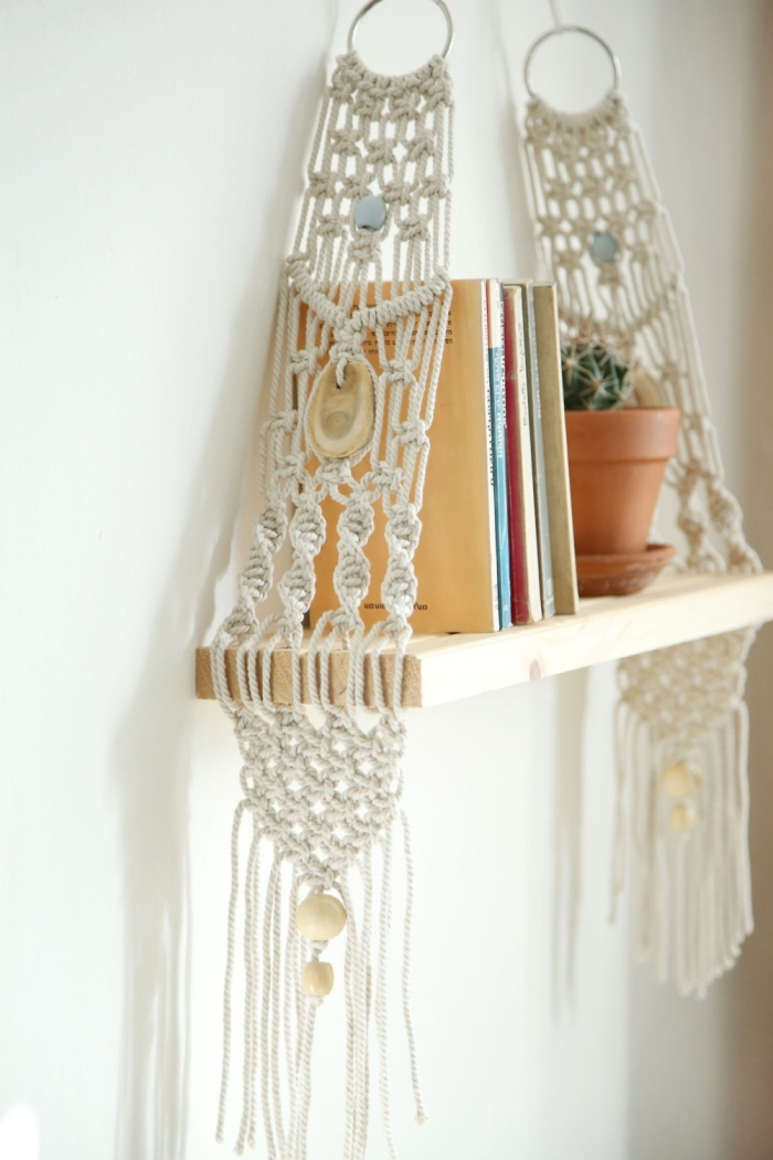 wooden hanging shelf, ceramic pot, stack of books, macrame wall hanging knots, white wall