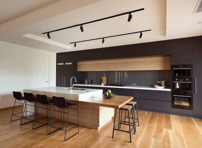 black cabinets, wooden floor, black metal bar stools, kitchen island with sink, grey backsplash