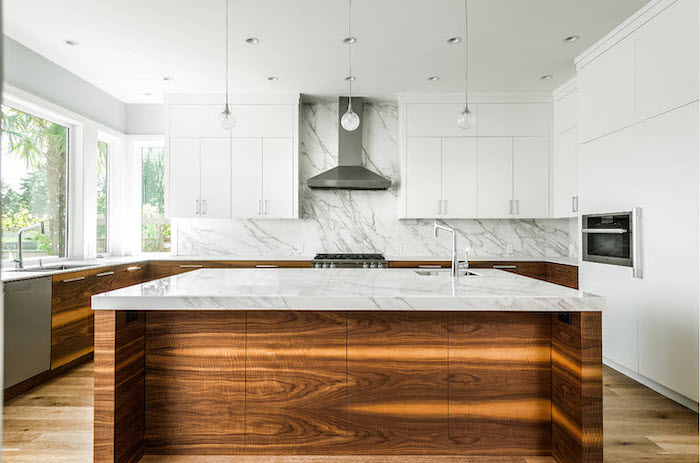 marble countertops and backsplash, white and wood cabinets, kitchen island with sink