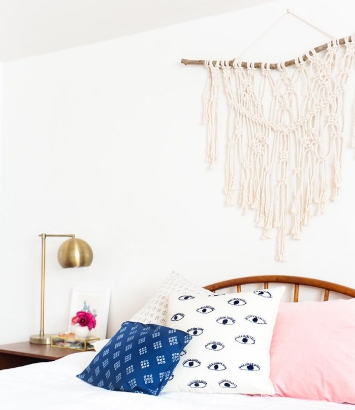 white pink and blue throw pillows, macrame wall hanging, white wall, brass metal lamp