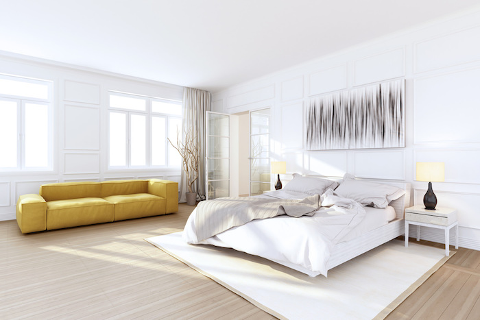 yellow leather sofa, wooden floor, master bedroom wall decor, white walls, white carpet, wooden night stand
