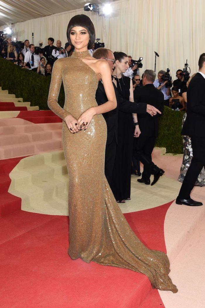 met gala 2017 theme, zendaya with short black hair, long gold dress, with one sleeve
