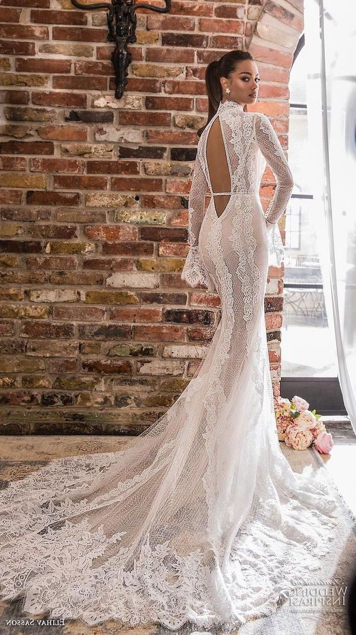 bare back, long lace train, chiffon wedding dress, black hair, in a high ponytail, brick wall