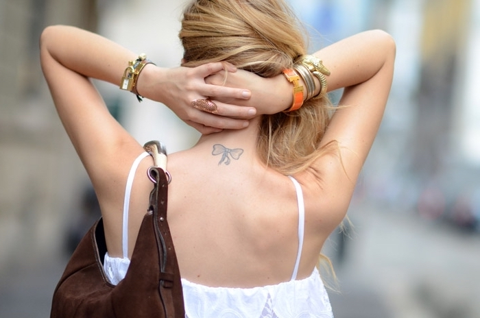 black bow, back tattoo, discreet tattoos, blonde wavy hair, brown velvet bag, white top
