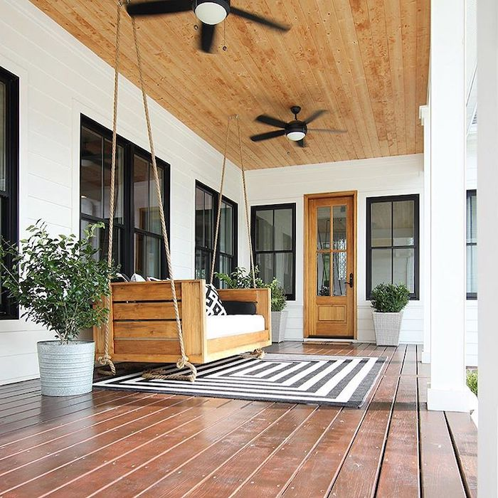 wooden swing, front porch decorating ideas, white cushions, black and white rug, wooden ceiling and floor
