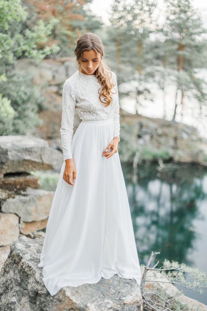 dark blonde hair, in a low ponytail, fitted wedding dresses, woman standing on rocks, next to a lake