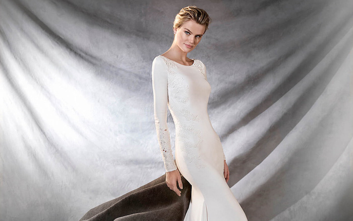 grey background, blonde hair, in a low updo, long sleeve lace wedding dress