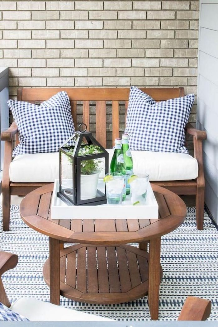 wooden bench and table, white cushions, blue and white throw pillows, brick wall, front porch decorating ideas
