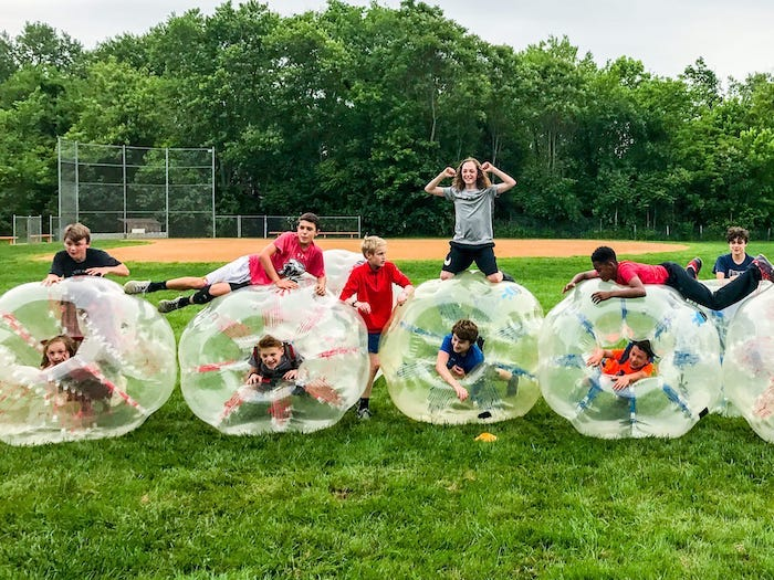 boys playing, on a green glass field, birthday party ideas for teens, bubble balls