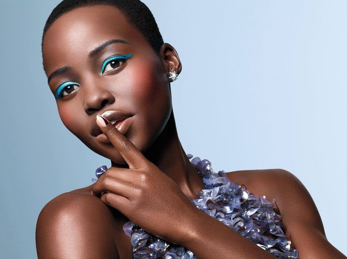 lupita nyong'o, blue eyeliner, purple dress, buzz cut, short haircuts for black women, blue background