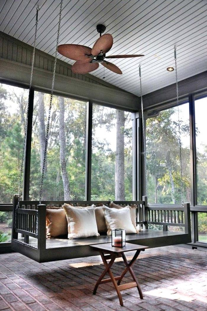 ceiling fan, front porch designs, wooden swing, held by metal chains, small table, screened in