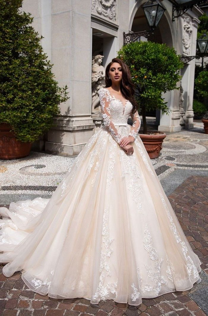 long brown wavy hair, ivory dress, made of tulle and lace, wedding dresses with sleeves