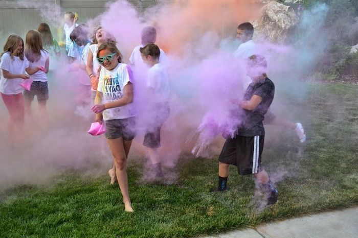 colourful smoke, children playing around, on green grass, birthday party themes, blue and purple smoke