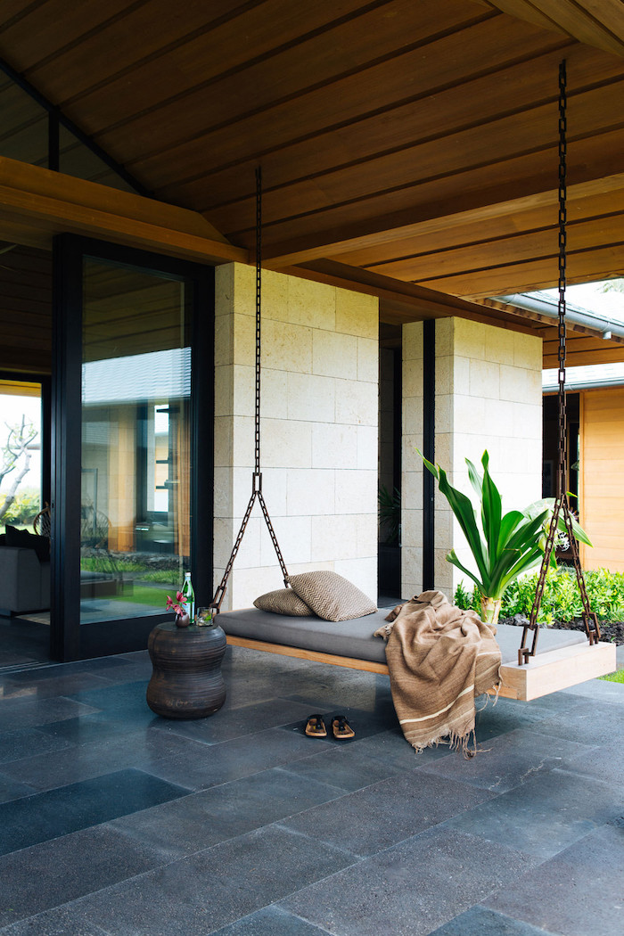 wooden swing, held by metal chains, front porch ideas, tiled floor, beige pillows and blanket