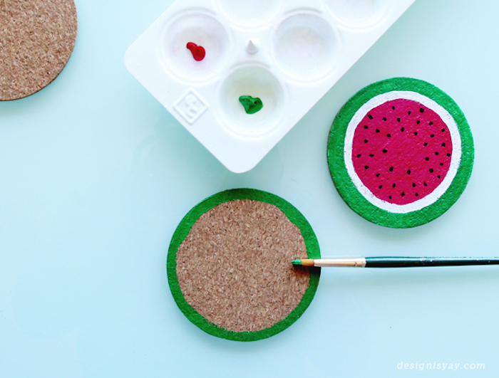 wooden coasters, easy diys, painted as watermelon, green and red paint, blue background