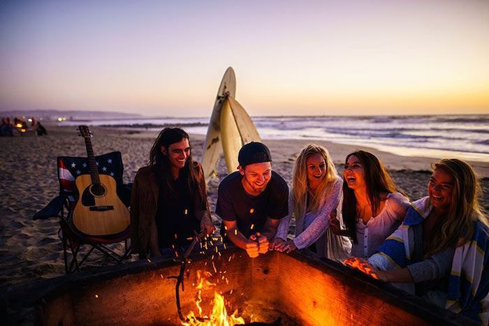 five people, gathered around a fire, on a beach, themes for parties, guitar on a chair, two surf boards