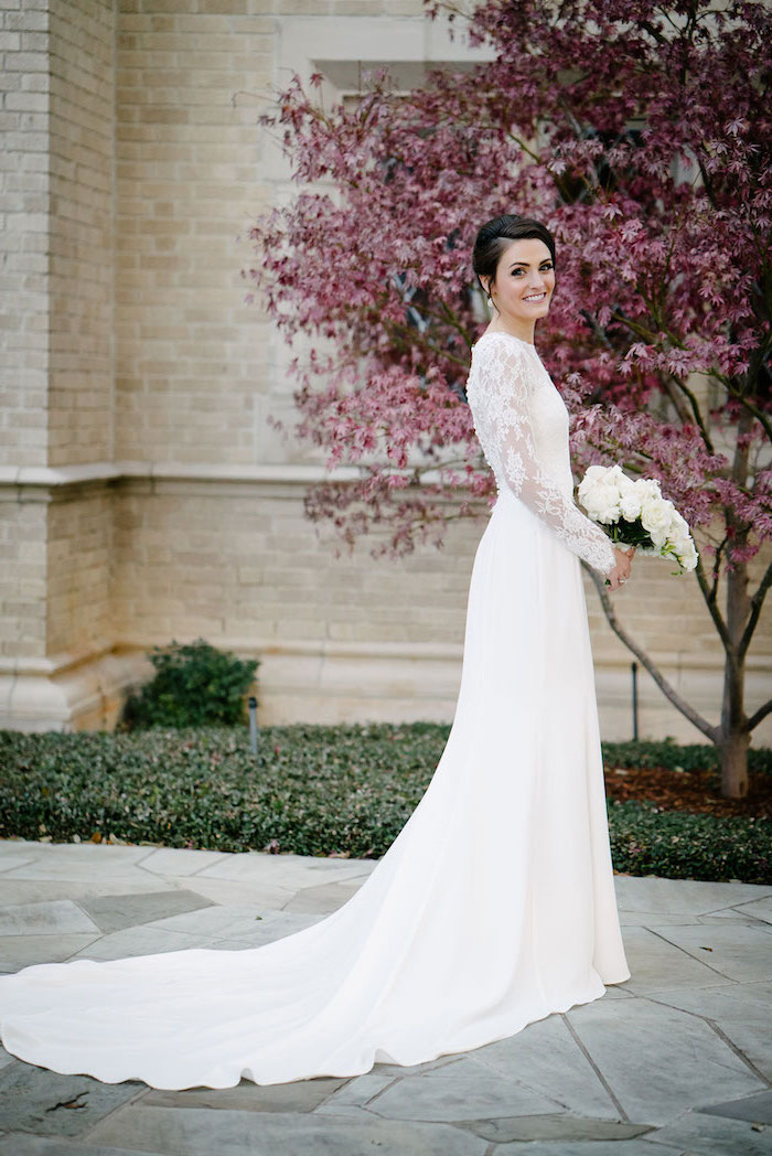 a line wedding dresses, white lace dress, long train, black hair, in a low updo, pink blooming tree, white flowers bouquet