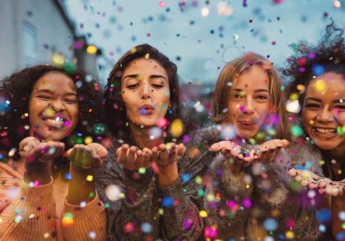 four girls, blowing kisses, colourful confetti around them, party theme ideas