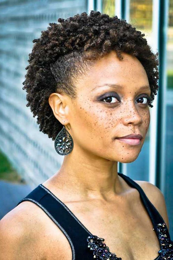 curly brown hair, short natural hairstyles, black top, black earrings, freckles on the face
