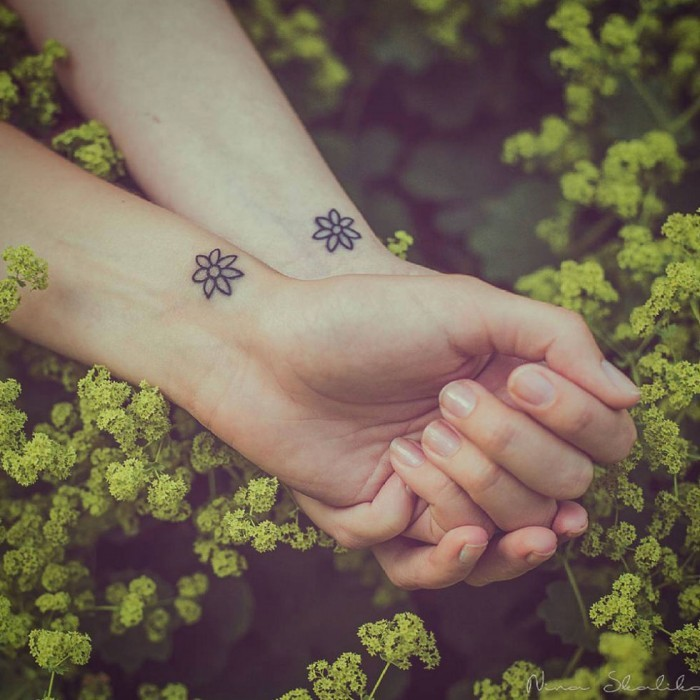 two flowers, wrist tattoos, small bestfriend tattoos, intertwined hands, green bush