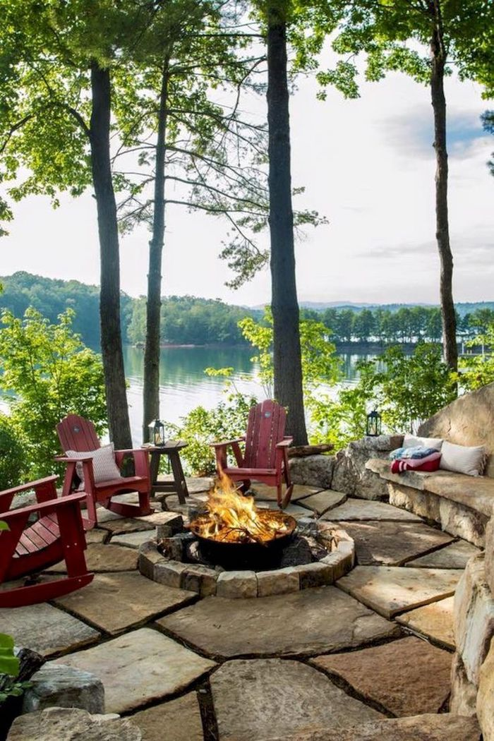 porch decorating ideas, wooden chairs, round fire pit, stone tiles floor, tall trees, over a lake