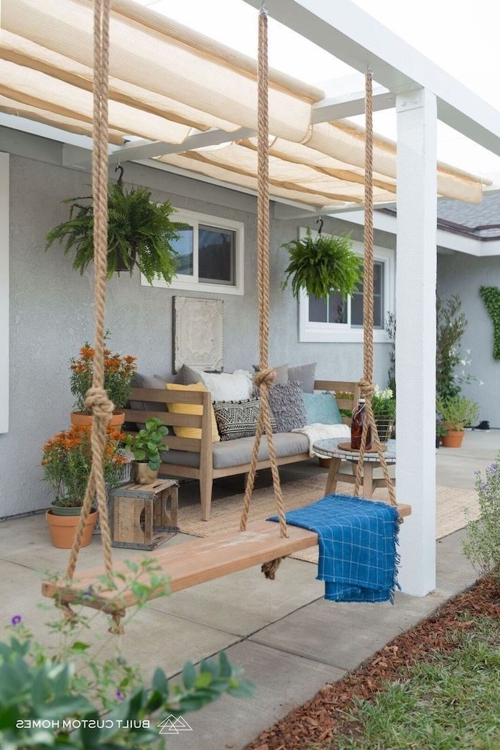 wooden swing, held by ropes, porch decorating ideas, blue blanket, grey cushions, colourful throw pillows