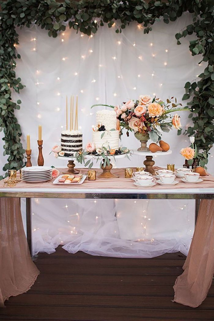 white tulle, fairy lights, greenery arch, flower bouquet, two tier cake, birthday party ideas for boys