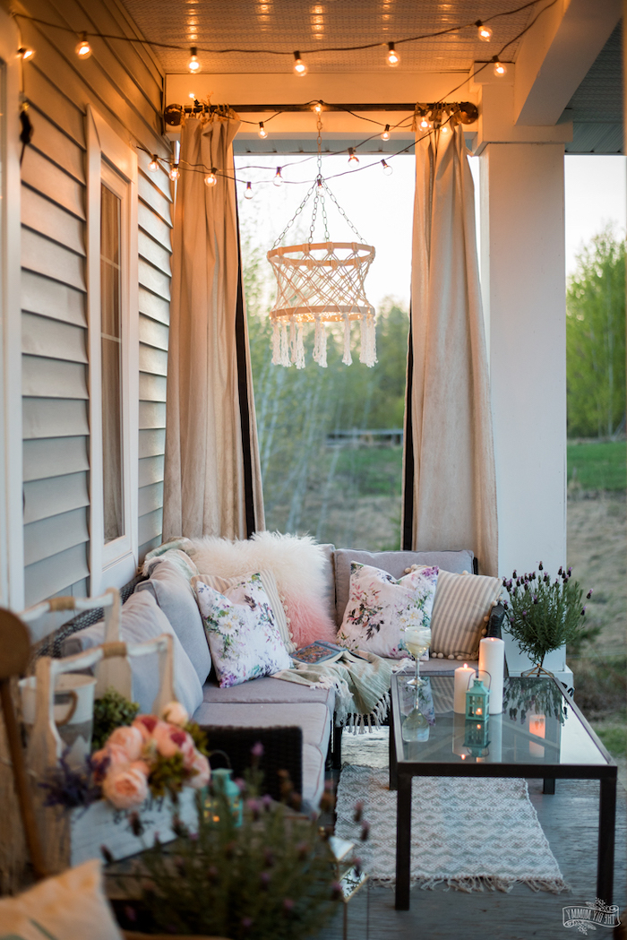 screened in porch designs, strings of lights, grey sofa, glass coffee table, flower bouquets