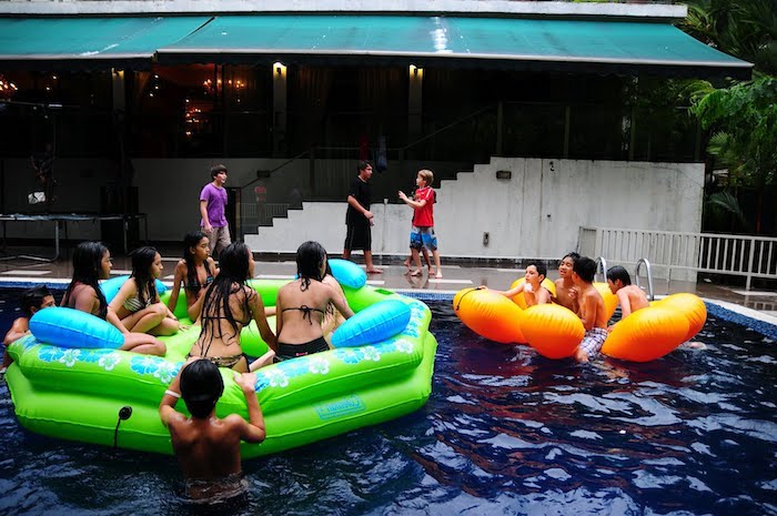pool party, themes for parties, children playing in a pool, green and orange floats