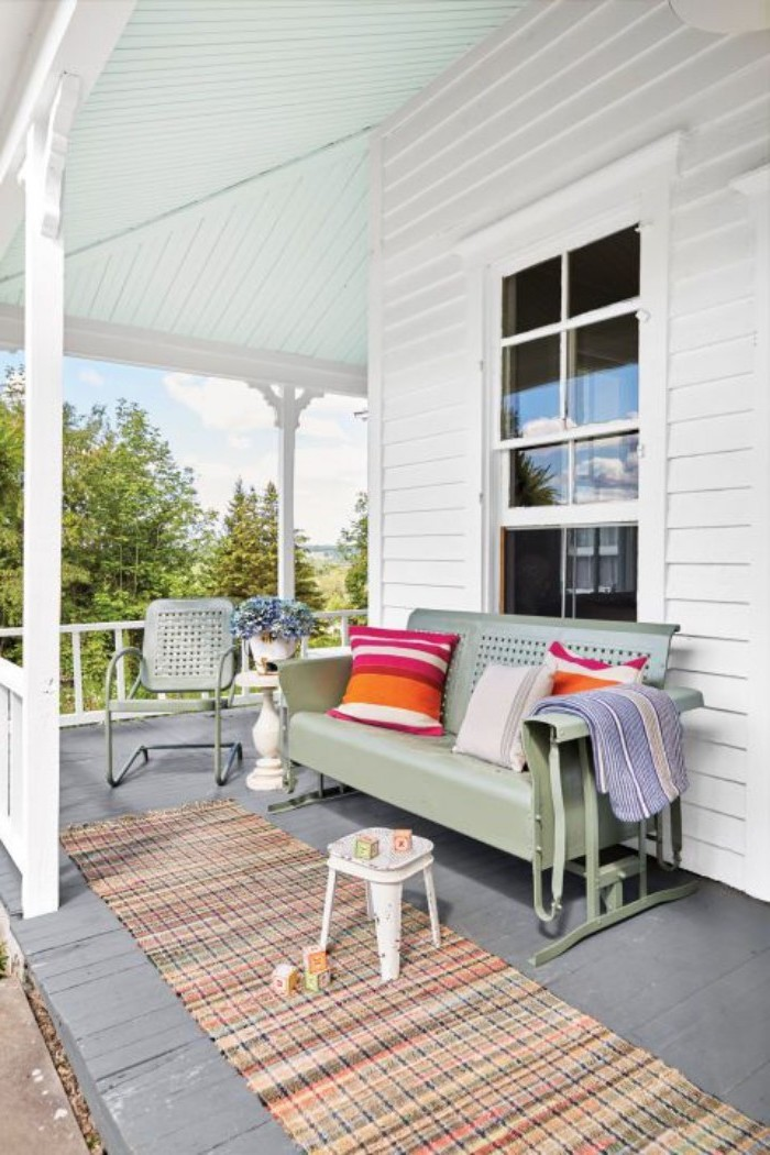 colourful rug, screened in porch designs, green metal sofa and chair, colourful throw pillows