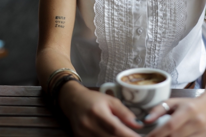 guts over fear, coffee cup, white shirt, inside arm tattoo, tattoo locations, wooden table