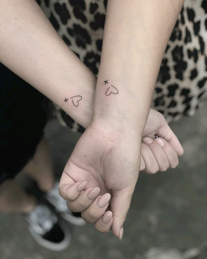friendship tattoos, hearts and airplanes, wrist tattoos, black and white photo