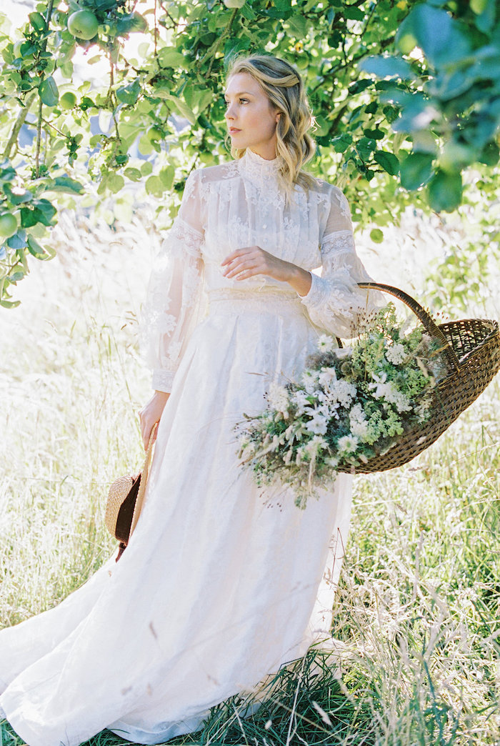 wooden basket, with white flowers inside, high neck, lace dress, blonde wavy hair, wedding dresses with long trains