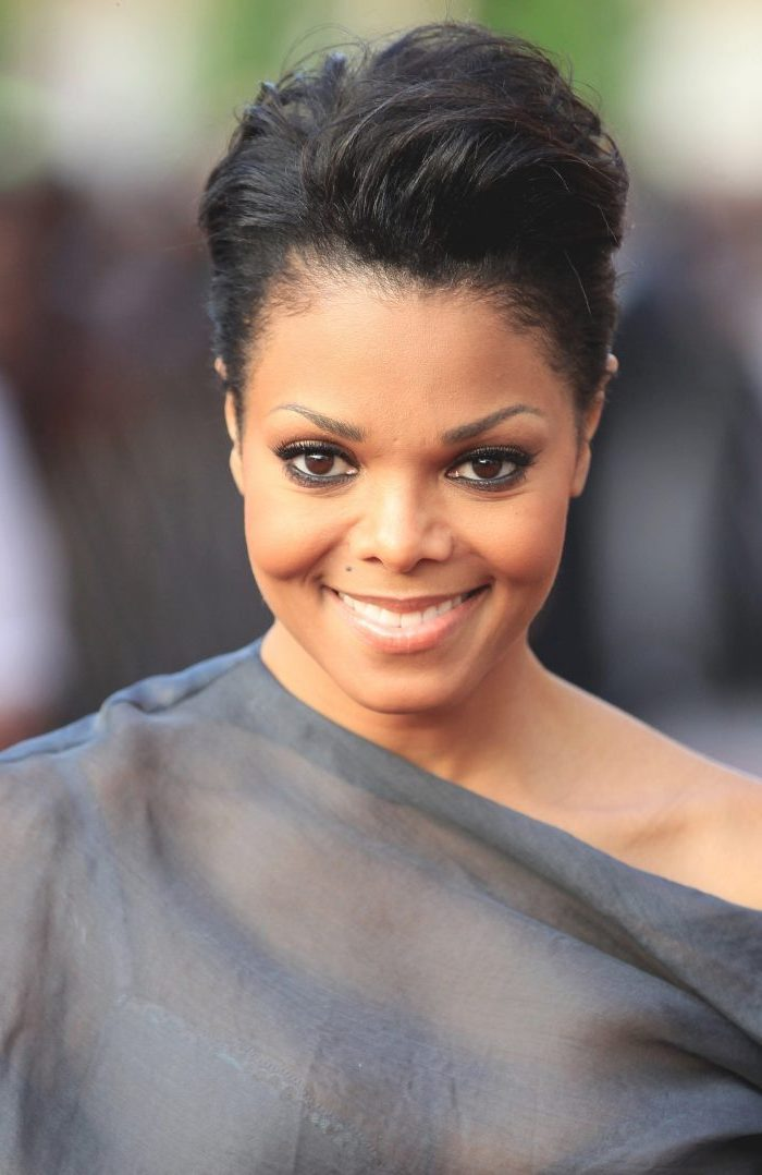 janet jackson smiling, wearing a grey dress, black hair, short curly hairstyles for black women