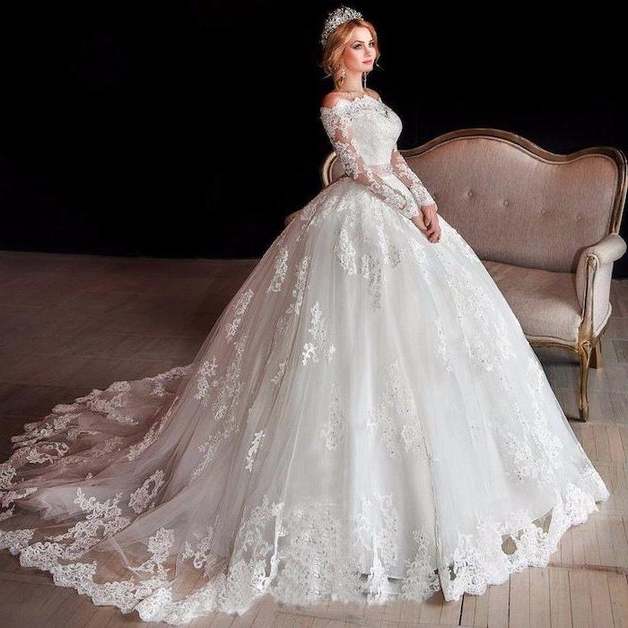 blonde hair, in a low updo, lace wedding dress with cap sleeves, grey sofa, lace and tulle