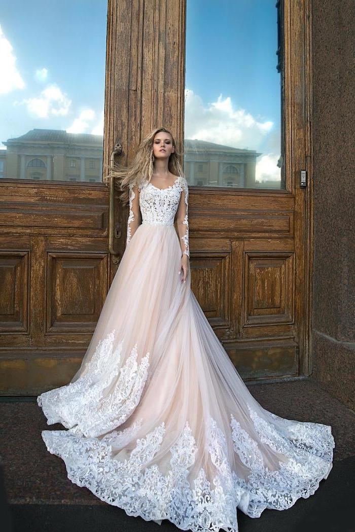 large wooden door, ivory dress, made of lace and chiffon, corset wedding dresses, long blonde wavy hair