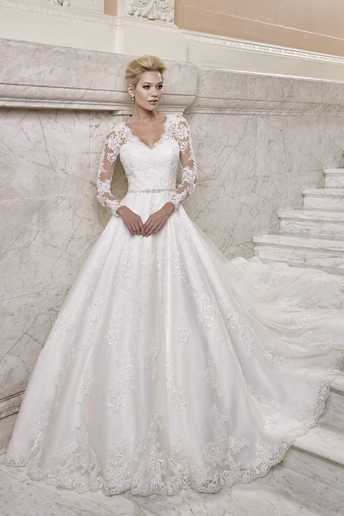 blonde hair, in a low updo, marble staircase, lace wedding dress with cap sleeves, v neckline