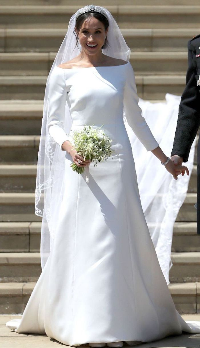 meghan markle, long train, white flower bouquet, long sleeve ball gown wedding dress, black hair, in a low updo