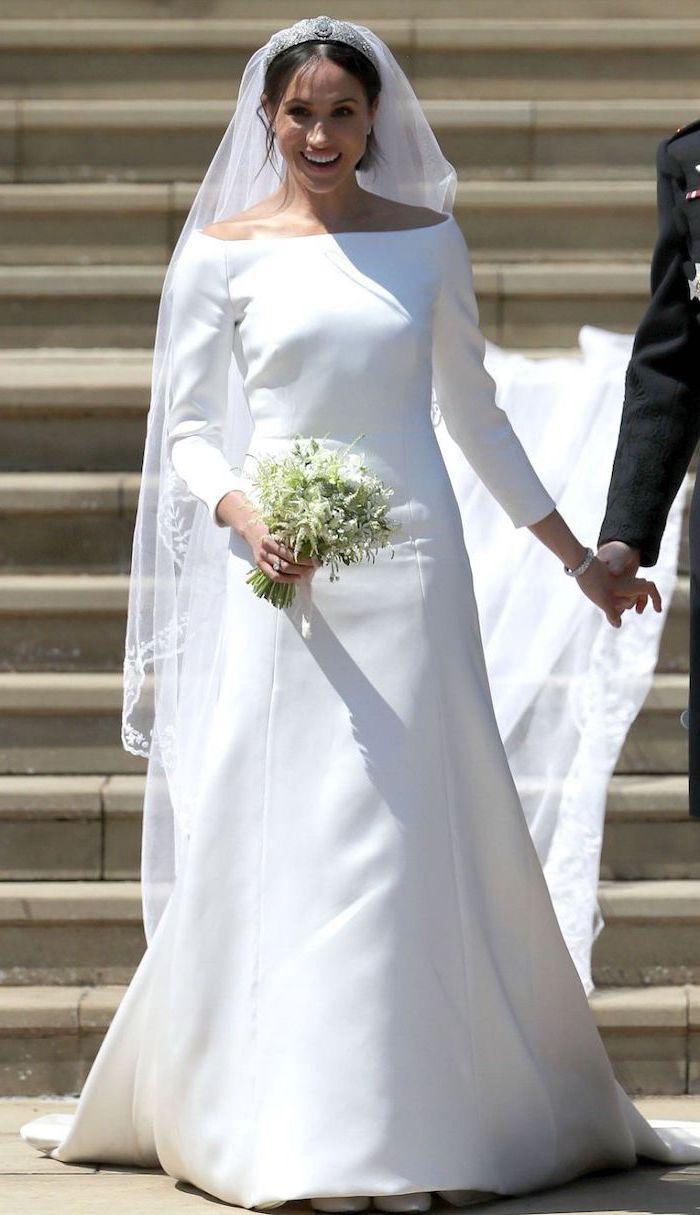 meghan markle, long train, white flower bouquet, long sleeve ball gown wedding dress, black hair, in a low updo