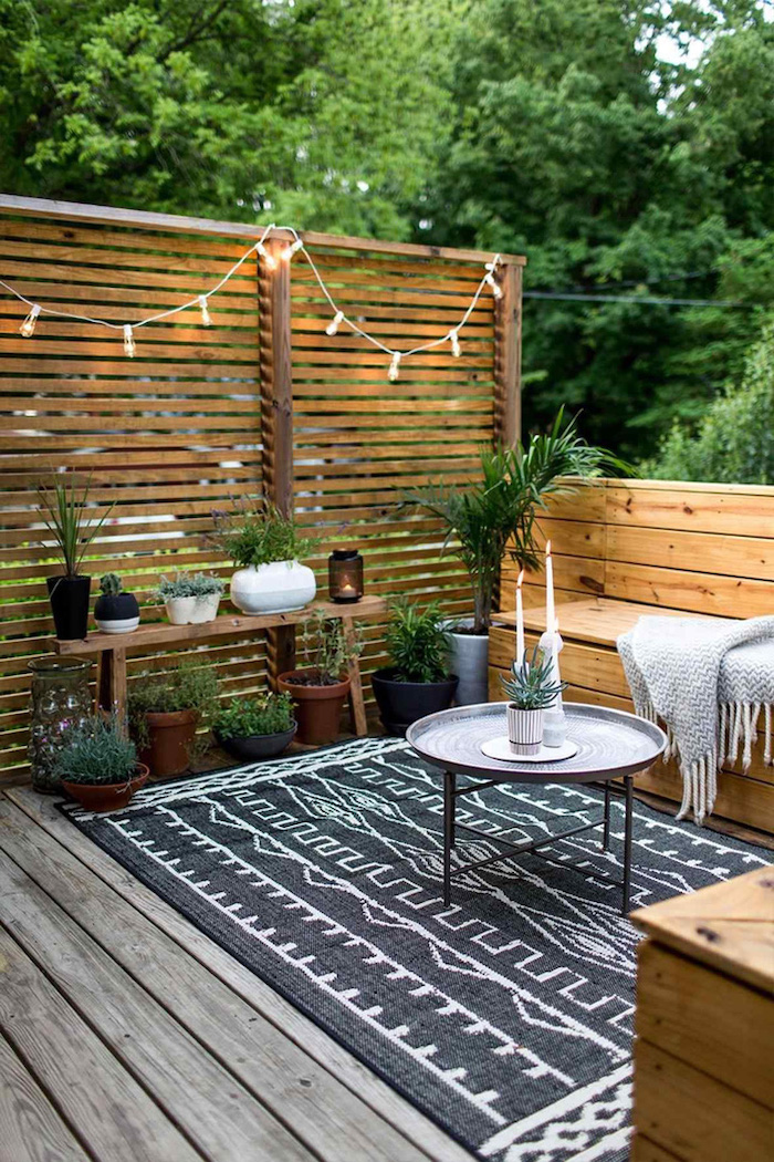 black and white rug, front door decor ideas, wooden divider, wooden benches, potted plants