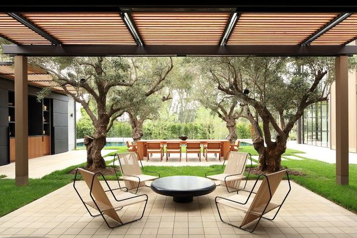 black metal chairs and table, tiled floor, outdoor covered patio, tall trees, large wooden table and chairs