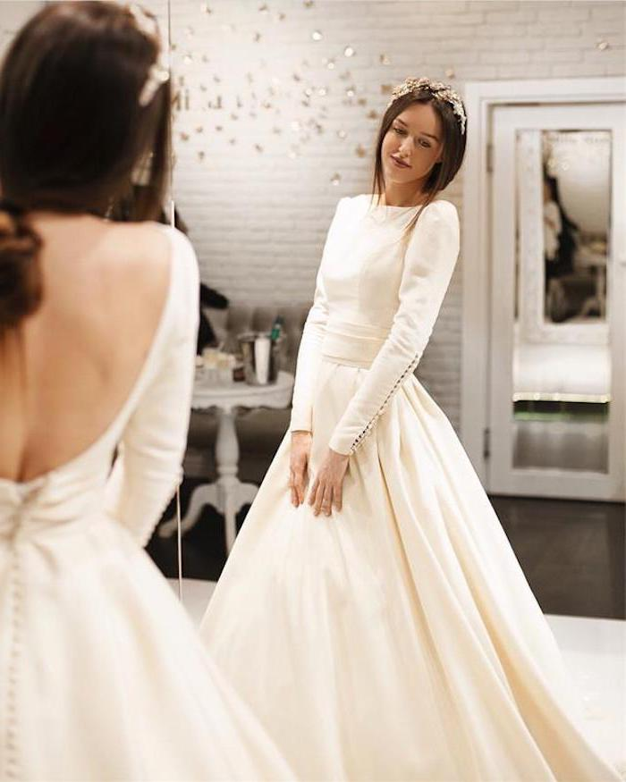 mirror image, bare back, long sleeve ball gown wedding dress, brown hair, in a low ponytail, hair accessory
