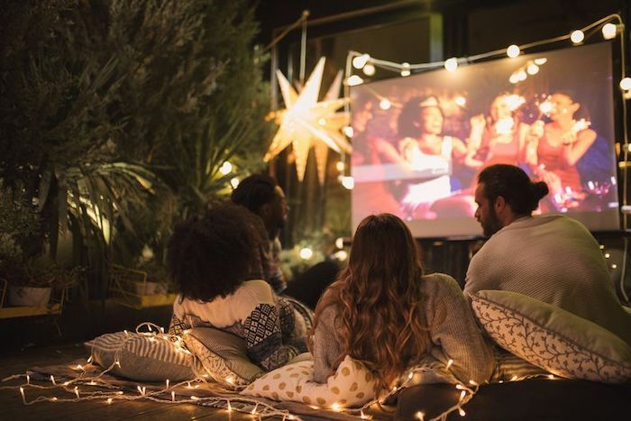 outdoor movie night, party theme ideas, strings of fairy lights, four people, sitting on pillows