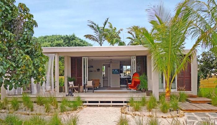 palm trees, beach house, orange wooden swing, outdoor covered patio, garden furniture