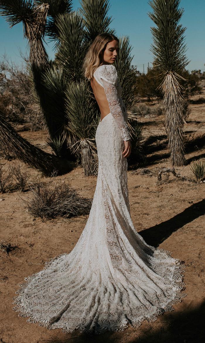palm trees, desert landscape, long sleeve ball gown wedding dress, bare back, long train, blonde wavy hair