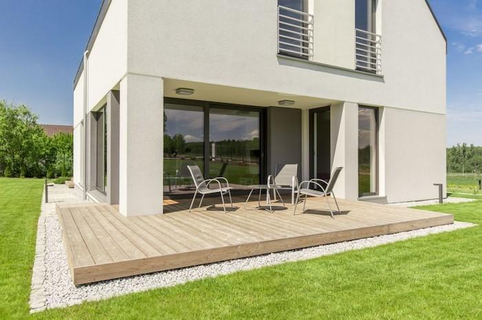 wooden floor, outdoor covered patio, metal garden furniture, green grass field
