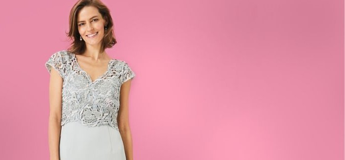 pink background, grey lace top, gold mother of the bride dresses, brown short wavy hair
