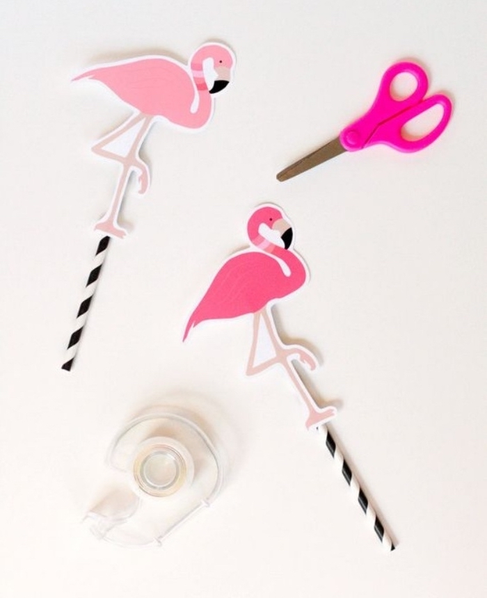 pink paper flamingos, on top of paper straws, diy crafts for teens, scotch tape, pink scissors