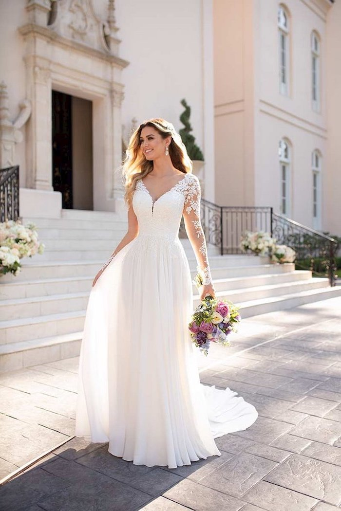 ball gown wedding dresses with sleeves, v neckline, long brown wavy hair, colourful flower bouquet